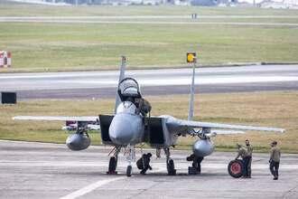パンクしたF15戦闘機のタイヤを交換する兵士ら=18日午前10時47分(提供)