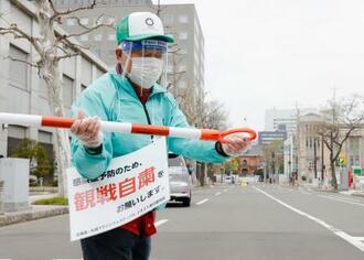 札幌市で開催される東京五輪マラソンのテスト大会で、観戦自粛を呼び掛ける案内を掲げて準備する関係者=5日午前