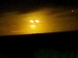 石垣島北部の水平線上空で目撃された謎の発光体=29日午後7時41分、石垣市久宇良(新垣信成さん提供)
