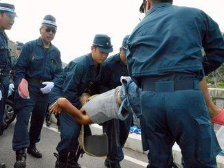 座り込みを続ける市民を3人がかりで持ち上げ、強制排除する機動隊=20日、東村・高江