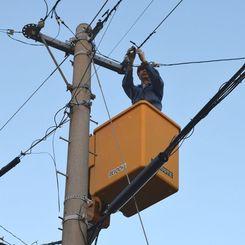 停電の復旧に向けて作業する電気工事会社の作業員=2日午後6時過ぎ、うるま市
