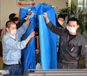 窃盗容疑などで愛知県で逮捕された18歳少年をブルーシートで覆い、車に乗せようとする県警捜査員=12日午後5時39分、那覇空港