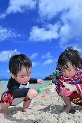 青空の下、波打ち際で砂遊びを楽しむ子どもたち=29日午前、北谷町のアラハビーチ(下地広也撮影)