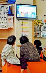 石垣市が設置した一時避難所で台風18号の関連ニュースを不安げに見つめるお年寄りら=13日正午ごろ、石垣市健康福祉センター