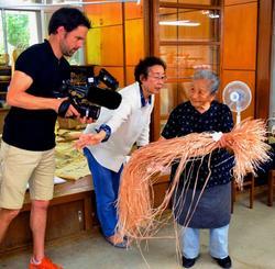 フランスのテレビ局の取材を受ける平良敏子さん(右)=15日、大宜味村喜如嘉