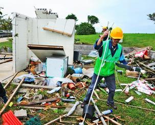竜巻とみられる強風で崩壊したプレハブ小屋を調査する沖縄気象台の職員=18日午後2時半、糸満市摩文仁の平和祈念公園(又吉健次撮影)