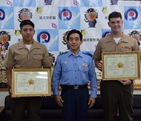 崎原永克署長から感謝状を受け取ったバーハン上等兵(右)とロサス一等兵=23日、浦添署