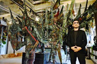廃棄衣料問題を扱ったアート展への来場を呼び掛ける小山健一郎さん=10日、国頭村辺土名・ヤンバルホステル