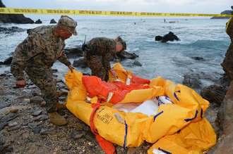 海上に残っていた脱出用ボートを片付ける米兵=14日午前7時5分、名護市安部の海岸