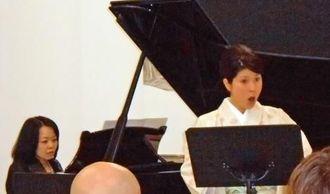 知念杉子さんのピアノ演奏で歌う大仲利江子さん(右)=ミラノ市のルチアーナ・マロン財団美術館