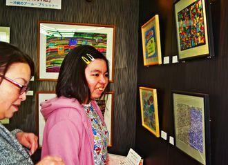 展示された自身の作品を見る新城千奈(右)と母由紀=20日、那覇市久茂地の琉球銀行本店