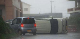 暴風で横転し、道路をふさいだ車=8日午後6時ごろ、名護市宇茂佐の森(浦崎直己撮影)(一部画像処理しています)
