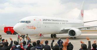 那覇空港に到着した737―800型機を出迎えるJTA社員ら=24日午後