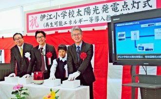 点灯式で笑顔を見せる(左から)島袋伊江村長、錦織研究企画係長、児童代表の屋嘉比君、古謝統括官=伊江村立伊江小学校