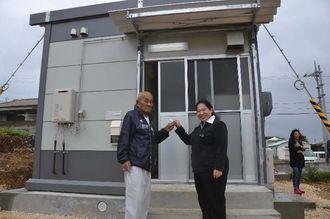 沖縄県の池田班長(右)から仮設住宅の鍵を受け取る上間徳助さん=与那国町、久部良地区