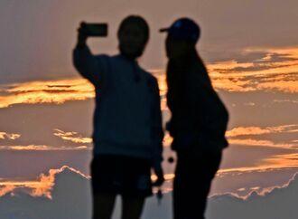 晴れ間が広がり、夕焼けをバックに記念写真を撮る若者=22日午後5時35分、豊見城市瀬長(国吉聡志撮影)