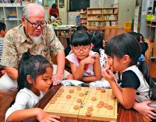 吉川正一さん(左)に教わりながら、象棋(チュンジー)の対戦をする長田児童クラブの子供たち=10日、那覇市長田