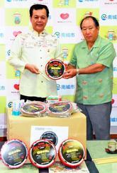 紙製パーランクーを寄贈したざまみダンボールの座間味勲社長(右)と古謝景春南城市長=21日、同市役所玉城庁舎