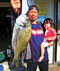 港川海岸で44.6センチ、1.49キロのミナミクロダイを釣った新里亮太さん(左)と羽美ちゃん=1月25日