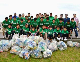 雨の中、消波ブロックの下まで掃除してゴミを集めたボランティアグループ・ホームの少年たち=18日、北谷町美浜