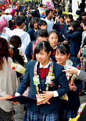父母らに祝福され、花道を歩く卒業生=9日、西原町・西原東中学校(金城健太撮影)