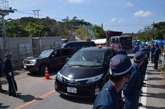 警察車両が前後を警備する中、N1地区表側出入り口から入るトラック=28日午前、東村高江