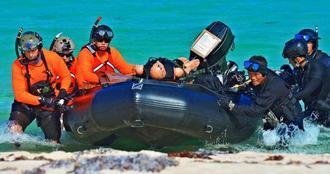 自衛隊と米軍の捜索救助共同訓練で、負傷者に見立てた人形をボートで搬送する自衛隊員(右側)と米兵=7日午前、うるま市浮原島(下地広也撮影)