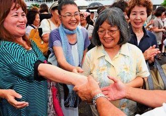 街頭で支持者と握手を交わす候補者=3日、本島南部