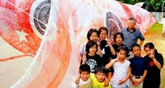 笑顔でポーズを取る子供たちと山内さん(中央奥)=19日、八重瀬町宜次の白川ハイツ自治会