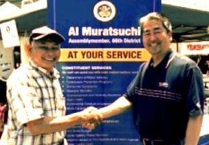 「私はウチナーンチュ」と話すアル・ムラツチ議員(右)と握手を交わす筆者=ガーデナ市のJCI