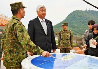 陸上自衛隊与那国駐屯地の発足を前に視察する中谷防衛相(左から2人目)=27日午後、与那国島