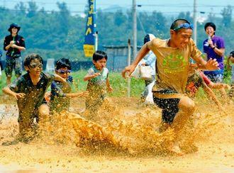 泥だらけになって田んぼの中を駆けっこする子どもたち=3日、金武町金武・ネイチャーみらい館(金城健太撮影)