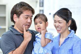 笑顔で記念撮影に納まる翁長希羽ちゃん(中)と、父親の司さん、母親の涼子さん=15日午後、沖縄県庁