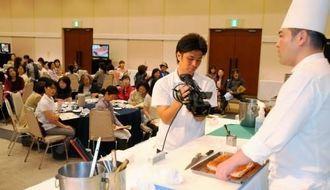 県産マグロや豚バラを使った料理を紹介する志喜屋譲さん(右)=22日、南城市・ユインチホテル南城