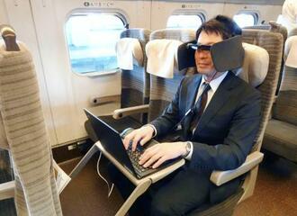 周囲の雑音を軽減するヘッドホンと、パソコンと連動する眼鏡型のディスプレー「スマートグラス」を装着して新幹線車内でのリモートワークを実演するJR東日本の社員=11日午後