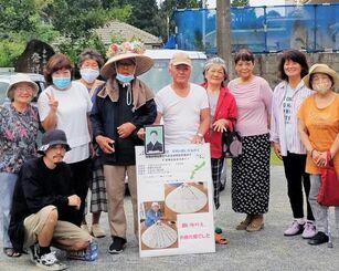 7日間の旅を終え、区民らとゴールを喜ぶ前田幸輝さん(右から6人目)=大宜味村・喜如嘉公民館