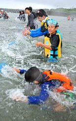 久高島伝統の追い込み漁で海面をたたき、魚を追い込む久高小中の児童・生徒=14日、南城市久高島