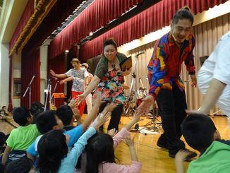 八重瀬町立白川小学校で公演。児童らとタッチするKachimbaのメンバーら=2015年