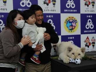 抽選で選ばれ、笑顔でホワイトライオンと記念撮影する親子連れ=26日、沖縄こどもの国