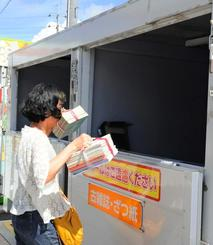 専用ボックスに古紙を投入する買い物客。買い物ついでに利用しているという=サンエー経塚シティ駐車場