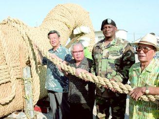 完成間近の那覇大綱挽の綱を手にする呉屋秀信さん(左から2人目)=2003年10月3日、那覇軍港