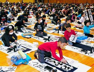 一文字ずつ集中して書き上げる参加者=5日午前、那覇市・県立武道館