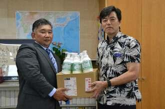 當間正和教育長(右)に除菌剤を手渡す教え子の松野信弘専務=25日、浦添市役所