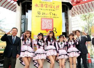NTT西日本の実証実験で、利用を呼び掛ける安部真弘東海事業本部長(右端)とアイドルグループ「OS☆U」のメンバーら=21日午後、名古屋市の大須商店街