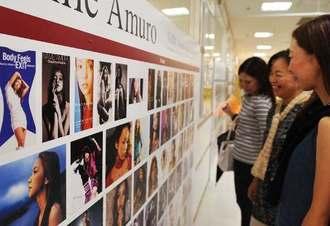 ジャケット写真を集めた写真展に見入る安室奈美恵さんのファン=21日、タワーレコード那覇リウボウ店