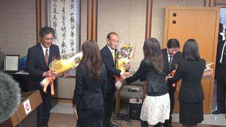 高良副知事(左)、川上副知事(右)とともに花束を受け取る仲井真知事=9日午前、沖縄県庁