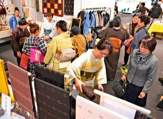 久米島紬の反物やシャツ、バックなどが並ぶ展示販売ブース=9日、那覇市久茂地・タイムスギャラリー