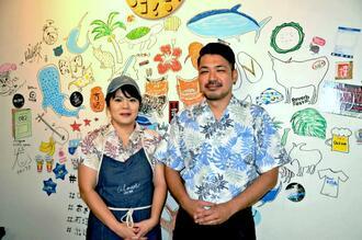 店内の白い壁に夫婦自らが描いたにぎやかな絵を背に笑顔を浮かべる新里翔太さん(右)、梨恵子さん=石垣市大川