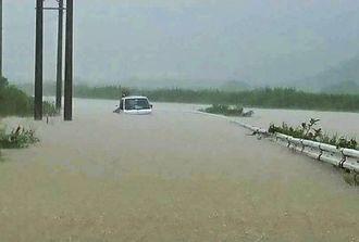 大雨で氾濫した与那国町の田原川(右)の流域=13日午前10時ごろ(同町提供)