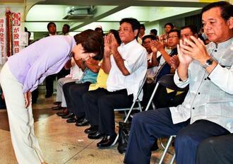 相手候補当確のテレビの速報を受け、支持者に頭を下げる島尻安伊子さん(左)=日午後8時2分、那覇市松山の選挙事務所